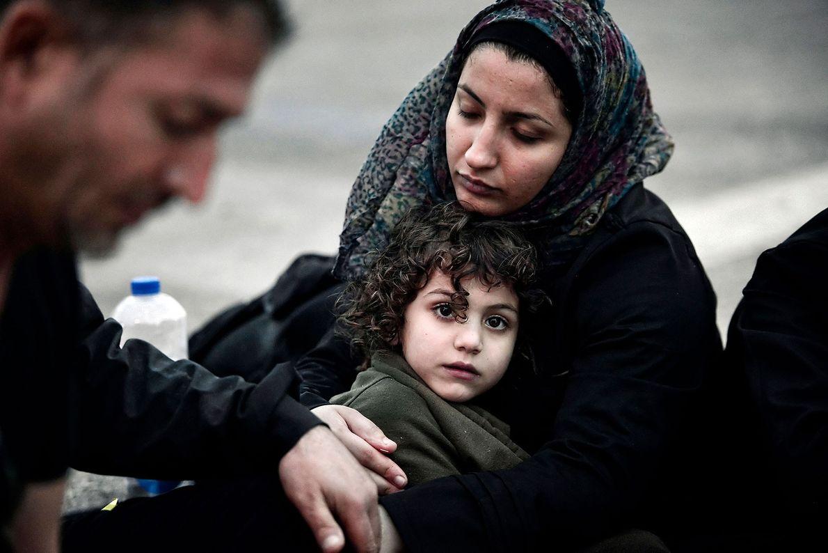 Eine syrische Mutter wärmt ihre Tochter