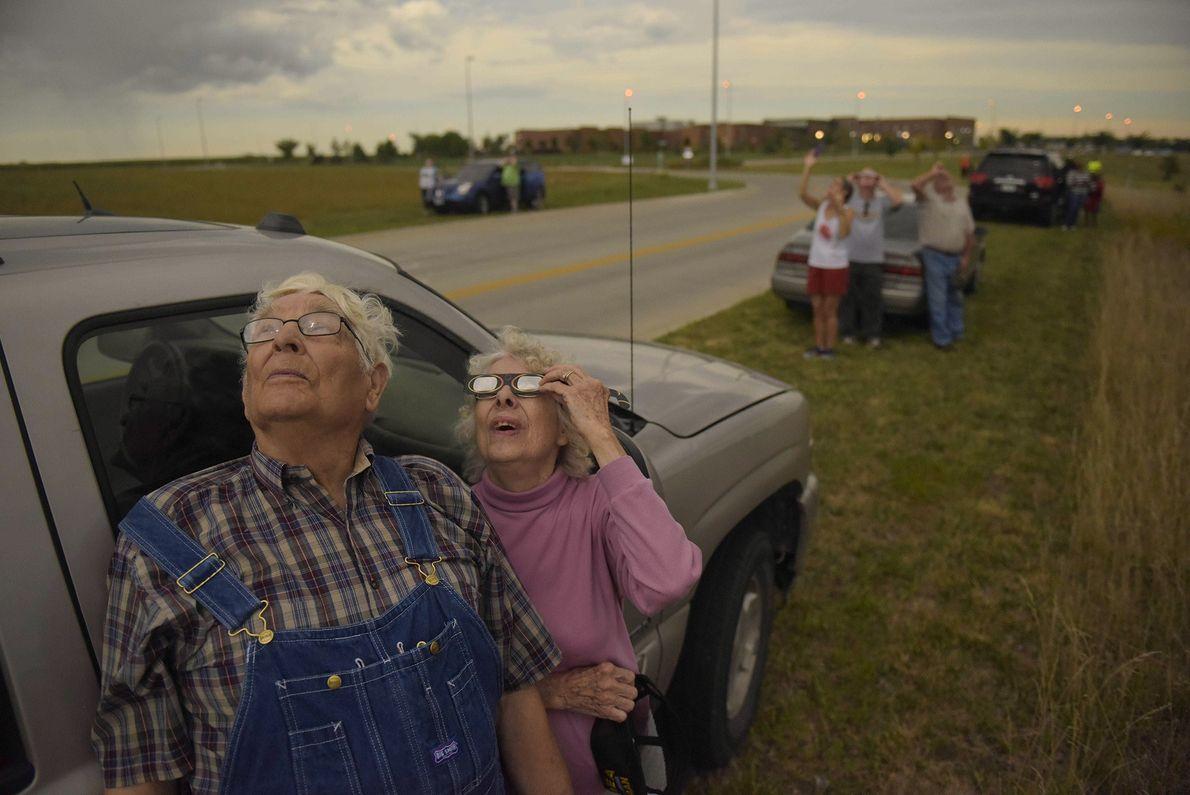 Wilfred und Audrey DeVries versuchen zusammen mit anderen am Straßenrand die Sonnenfinsternis durch den bewölkten Himmel ...
