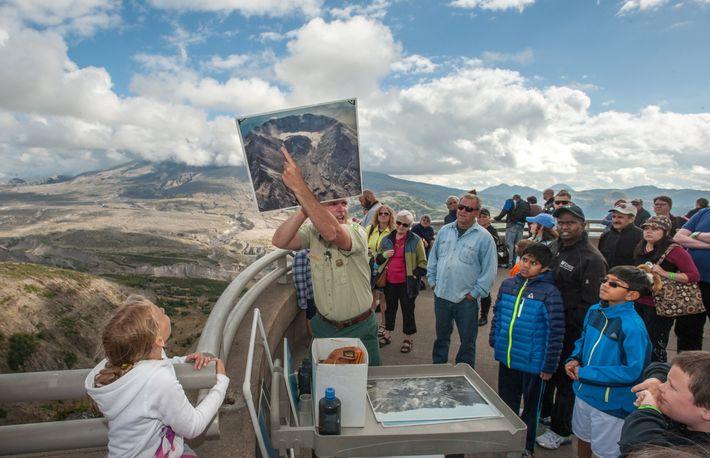 Ein Ranger hält ein großes Foto hoch, das den östlichen und westlichen Arm des Kratergletschers zeigt, ...