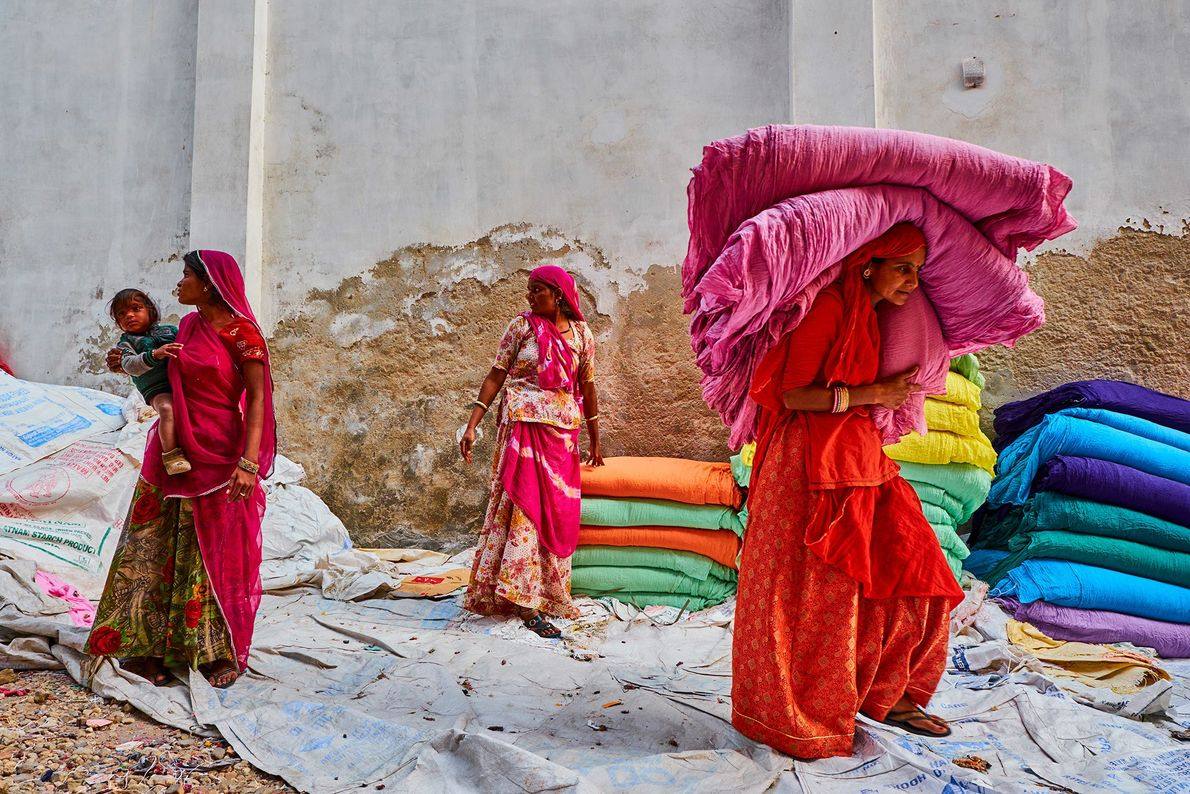 Women in Rajasthan gather up freshly dried saris at a factory. Before chemical dyes were introduced ...