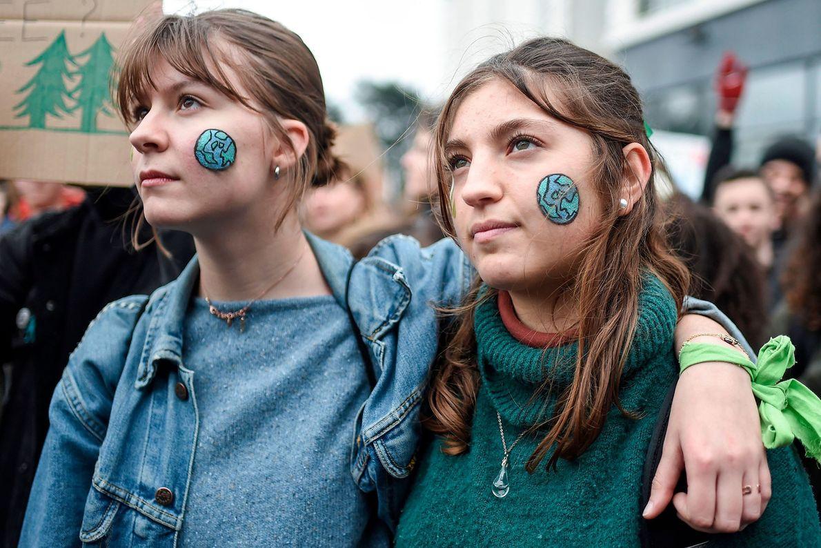 Im französischen Nantes haben sich Demonstranten die Erde auf die Wangen gemalt.