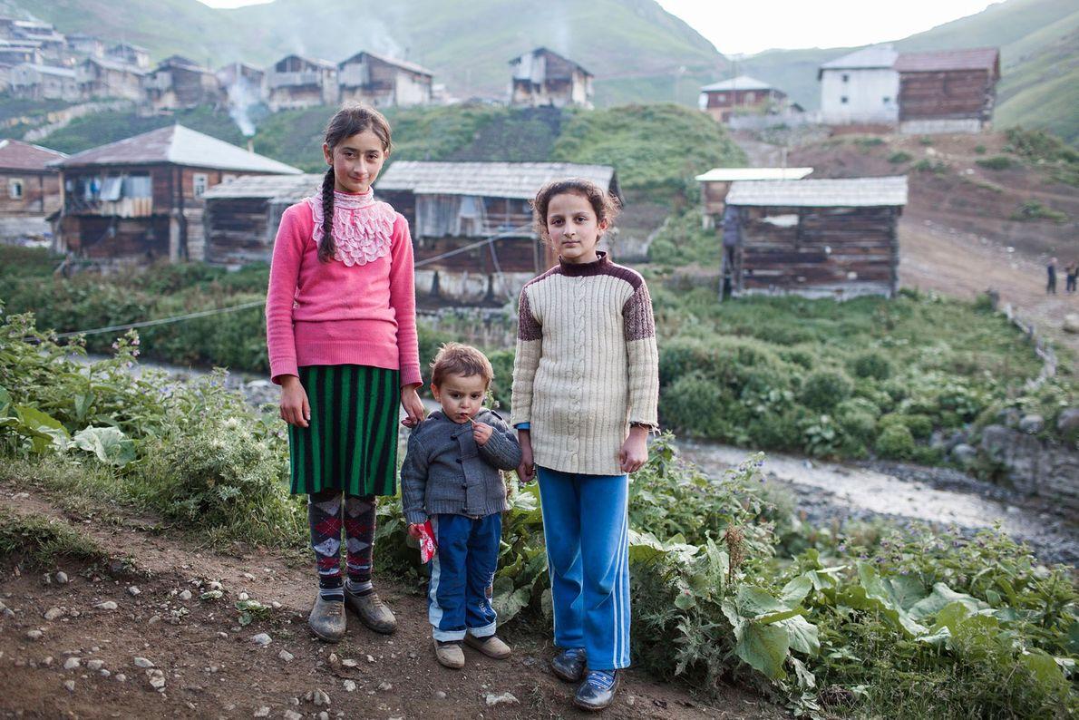 Foto von drei Kindern, die vor einem Dorf stehen