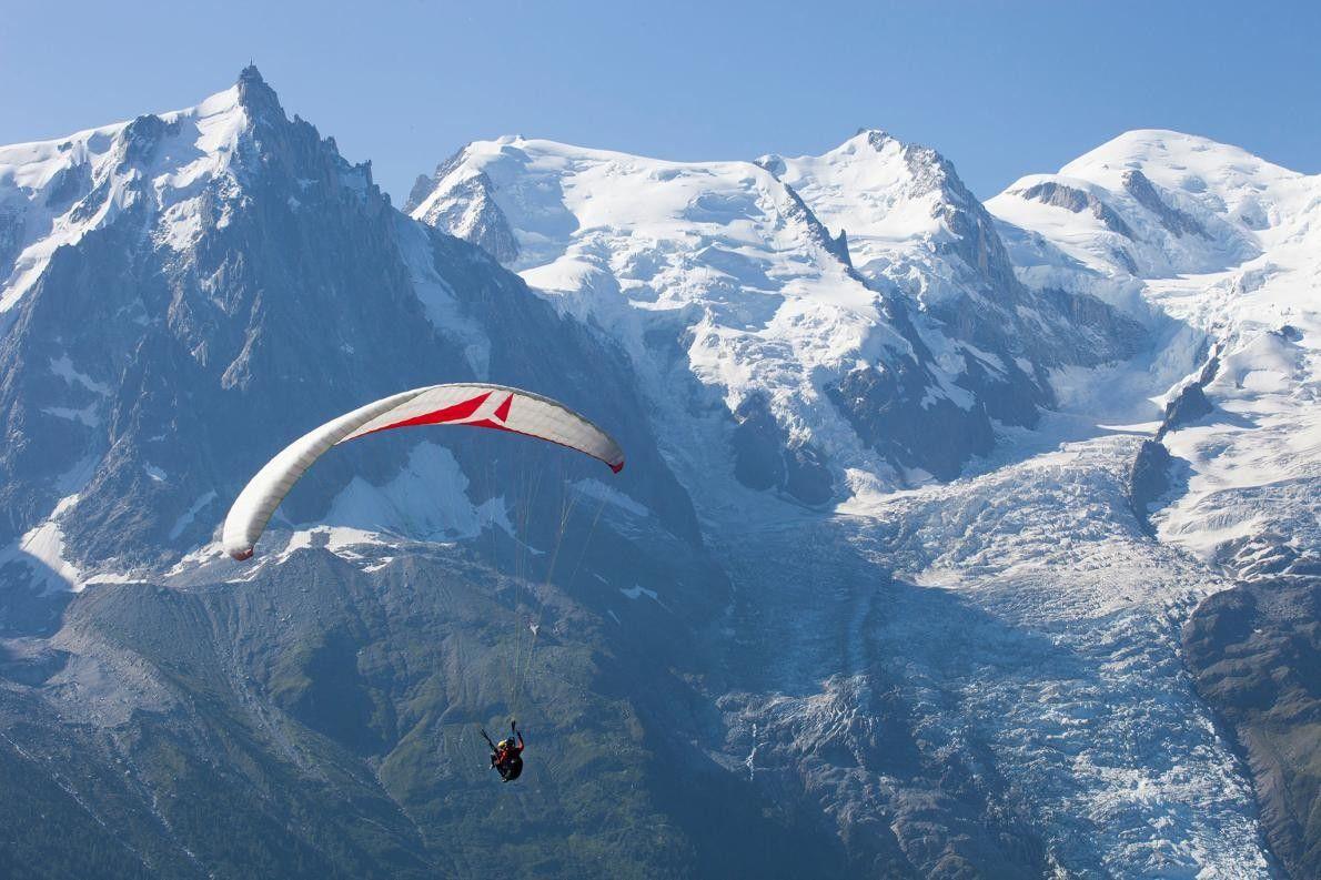 Ein Paraglider segelt über das Tal von Chamonix im Südosten Frankreichs und genießt die Aussicht auf ...