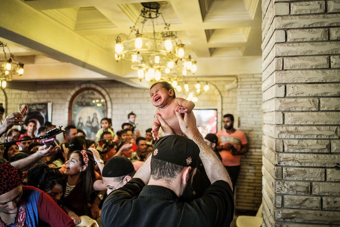 Priester hält Baby in Luft