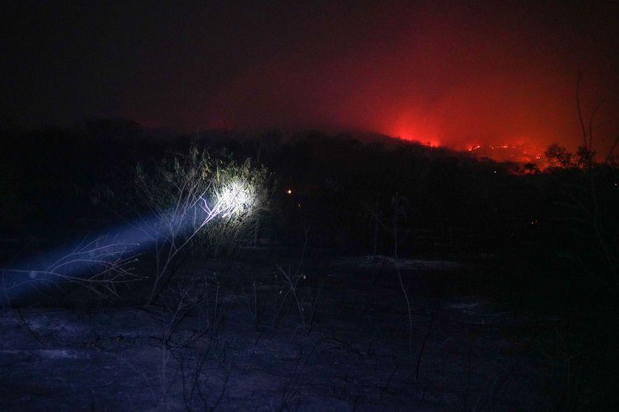 Freiwillige Feuerwehrleute aus Roboré bahnen sich mit Taschenlampen den Weg zum Brand.