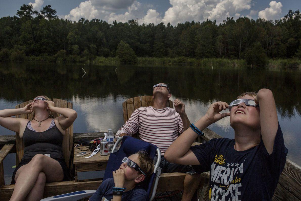 Eine Familie aus Kopenhagen, Dänemark, beobachtet die Sonnenfinsternis in Cross, South Carolina, am Lake Marion.