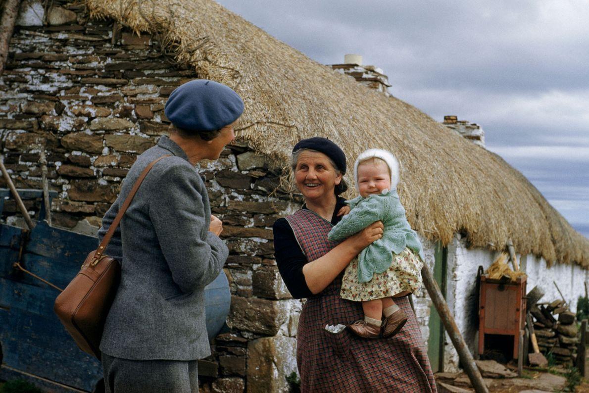 Eine Großmutter und ihr Enkelkind begrüßen eine Besucherin vor ihrem Hof in Schottland. 1956.