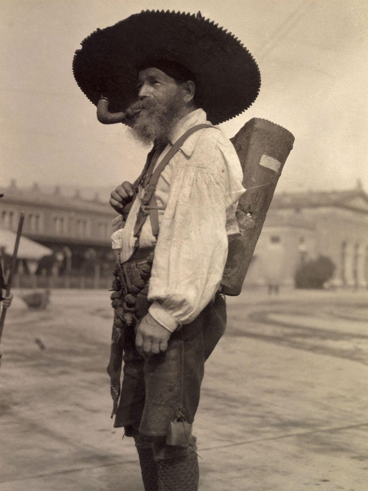 Ein Pfeife rauchender Österreicher trägt traditionelle Lederhosen und einen großen Hut.