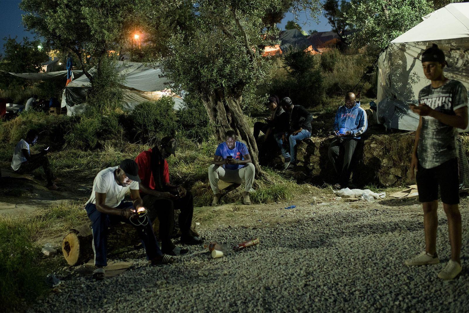 Die Bewohner des provisorischen Lagers, das Olive Grove genannt wird, versammeln sich dort, wo der Empfang ...