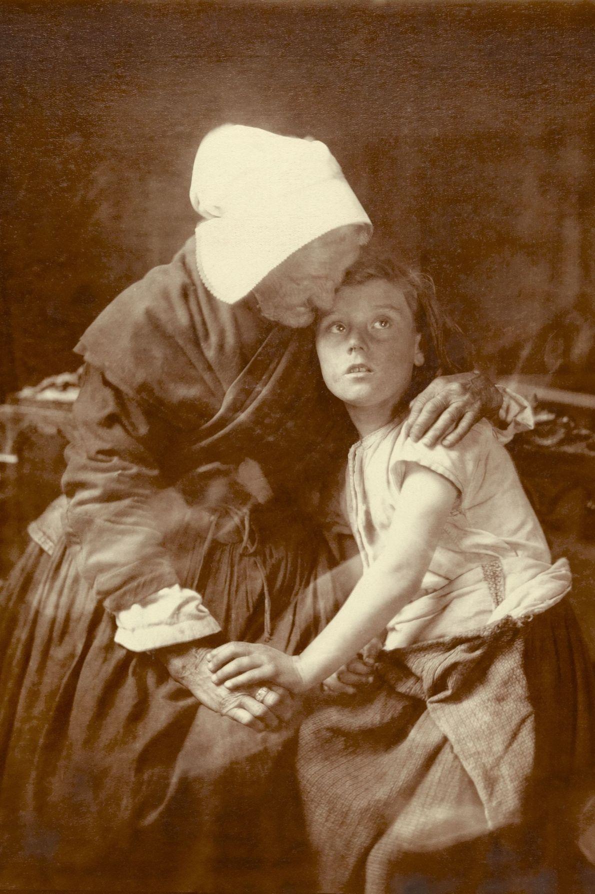 In Flandern umarmt eine alte Frau ein Kind.