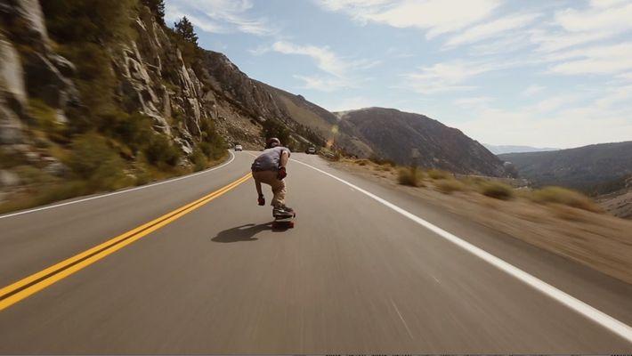 Downhill: Skater saust im Affenzahn einen Berg hinunter
