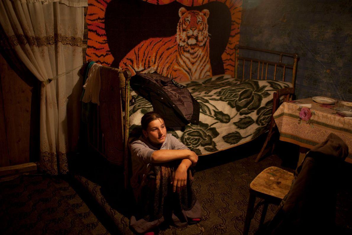 Foto von einem jungen Mädchen, das in ihrem Zimmer sitzt.