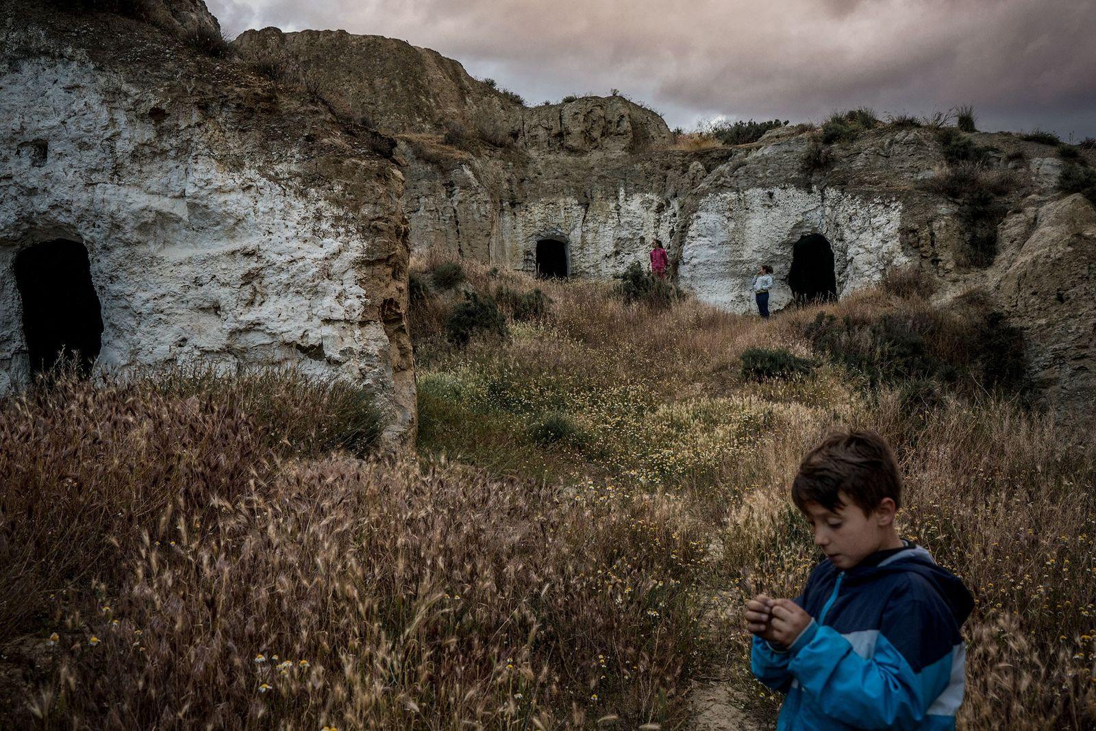 Kinder spielen in verlassenen Höhlen neben ihren eigenen Höhlenwohnungen. Früher war jede Höhle bewohnt, aber mittlerweile ...
