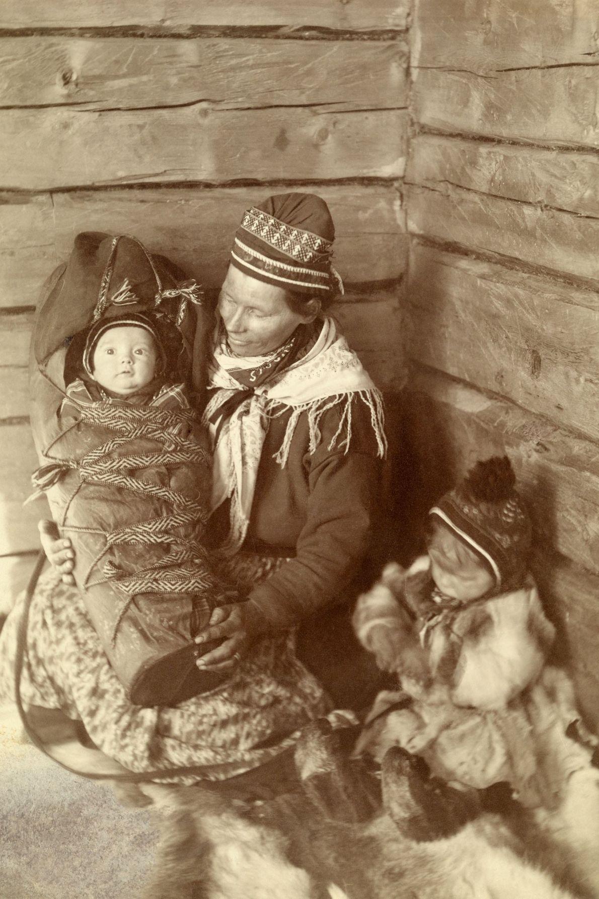 Eine Samin in der finnischen Landschaft Lappland sitzt mit ihrem Baby und ihrem Kleinkind auf weichen ...