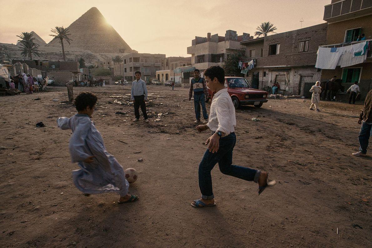 Dorfkinder spielen in Ägypten Fußball, während im Hintergrund die Sonne hinter den Pyramiden von Gizeh untergeht.