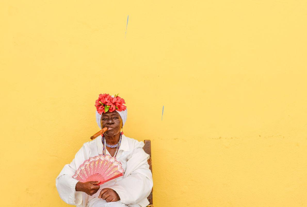 Eine kubanische Frau sitzt vor einer gelben Wand