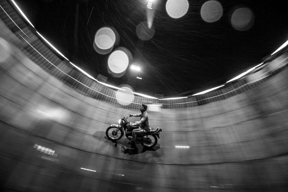 Ein Mann fährt an den Wänden eines leeren Brunnens Motorrad