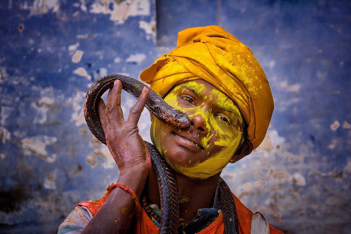 Ein indischer Junge hält eine Schlange beim Holi-Fest
