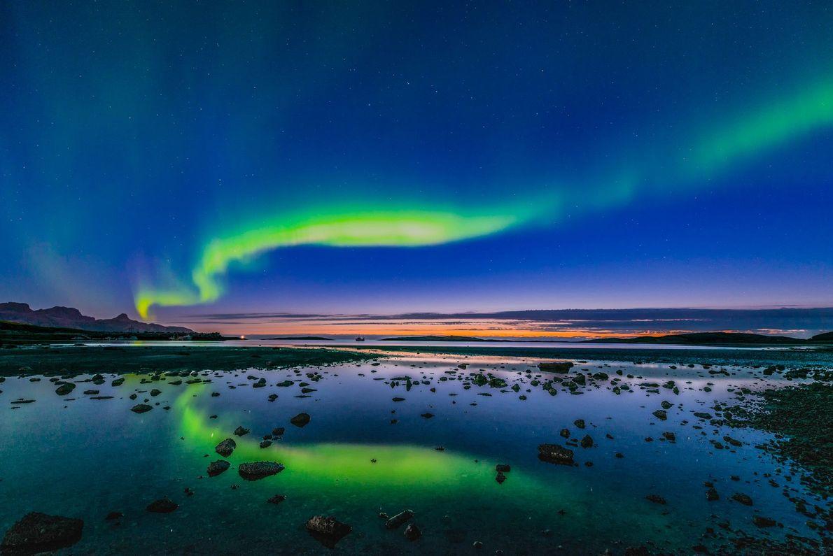 Nordlichter während eines Sonnenuntergangs über einem See