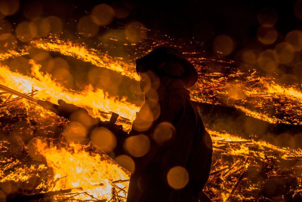 Ein Feuerwehrmann kämpft gegen ein Lauffeuer