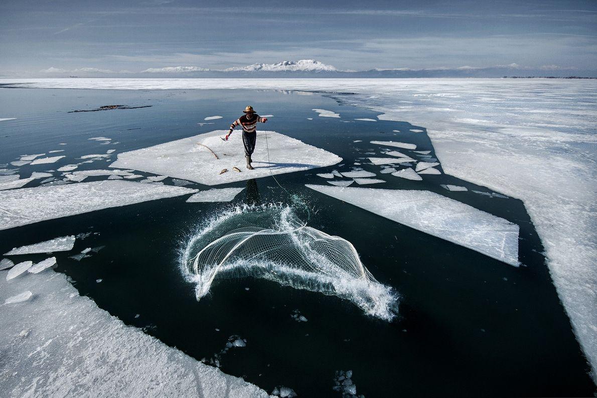 Ein Fischer auf einer Eisscholle wirft sein Netz aus