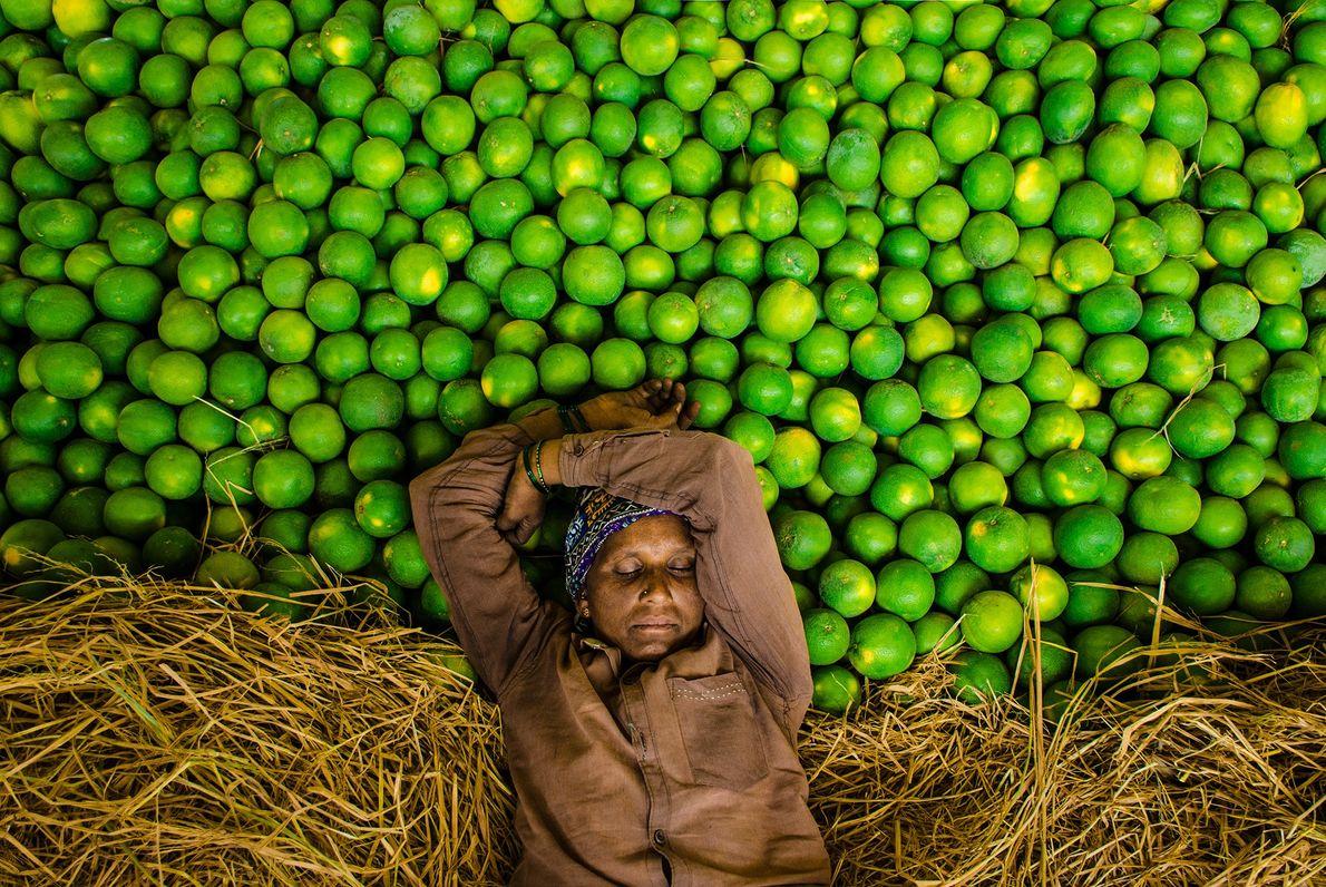 Eine schlafende Obstverkäuferin in Indien