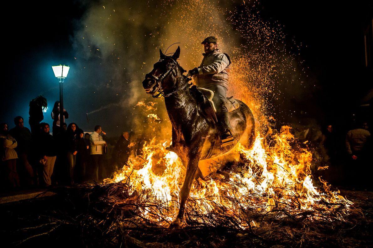 In Spanien reitet ein Mann mit einem Pferd durch Flammen