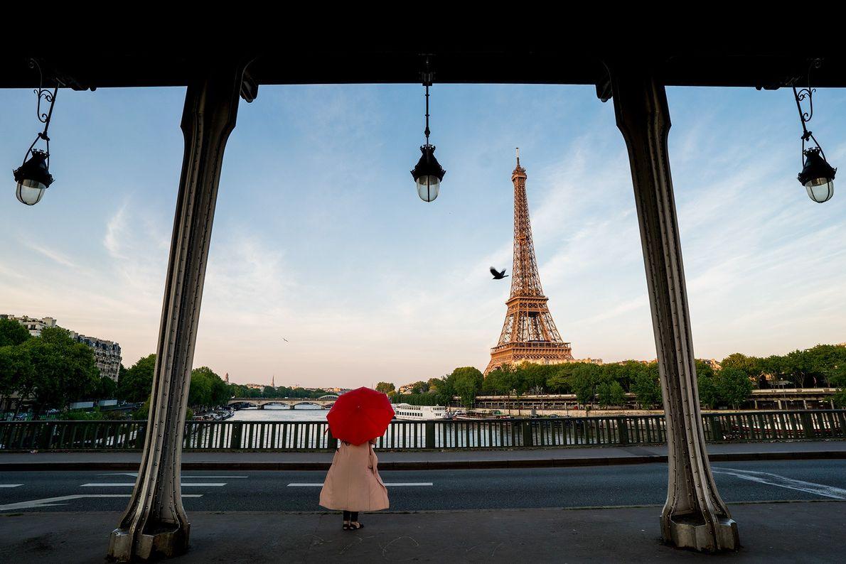 Person mit einem roten Regenschirm vor dem Eiffelturm
