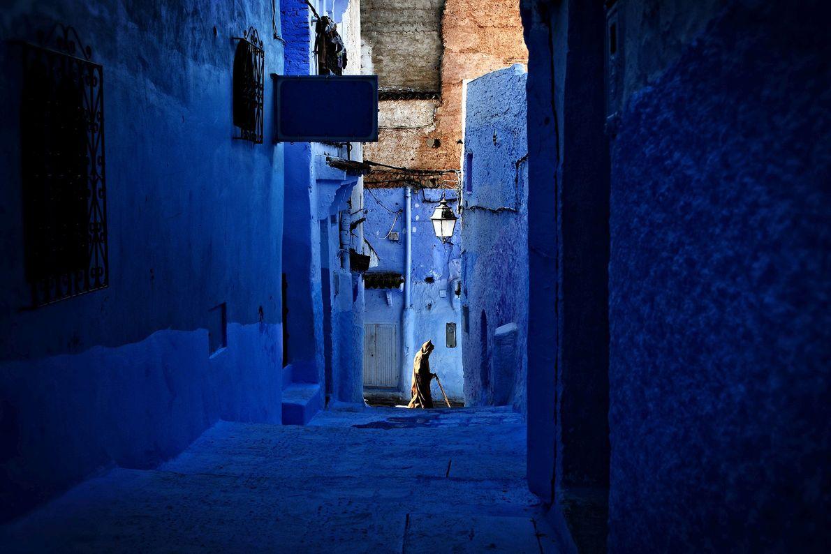 Ein Mann läuft eine blaue Gasse in Marokko entlang