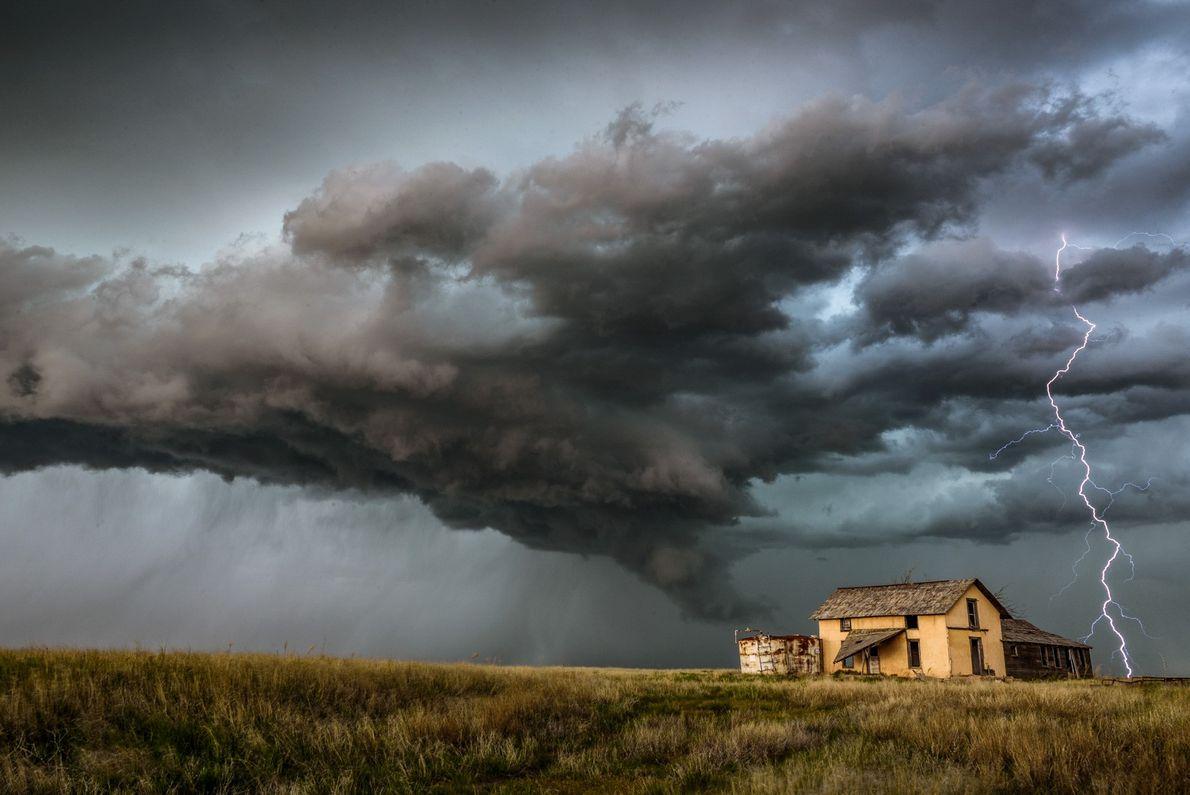 Ein Blitz schlägt neben einem Haus im Boden ein