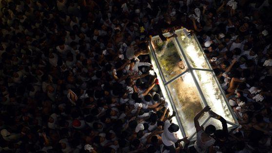 Menschen umringen einen Glaskasten mit einer Figur von Jesus