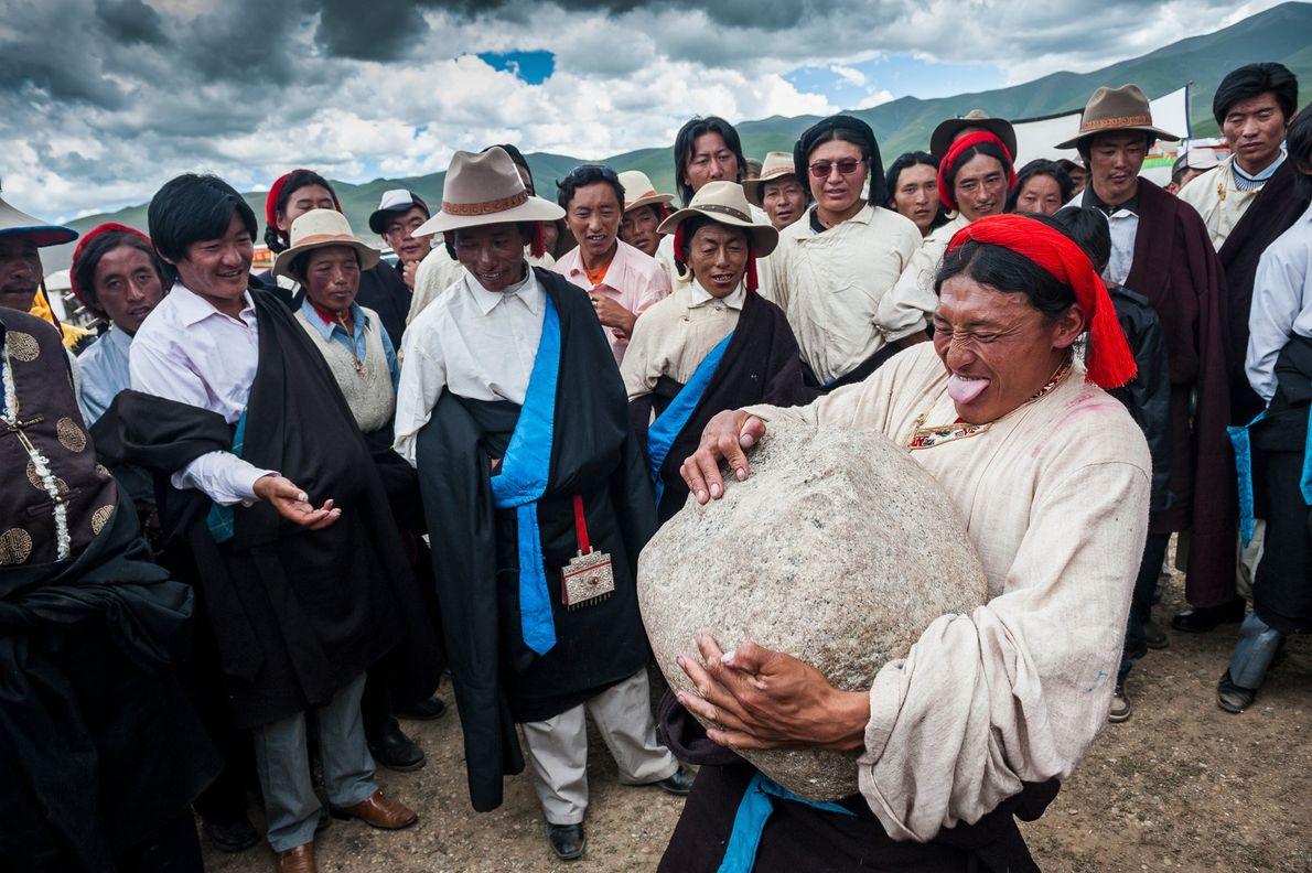 Ein Tibeter hebt einen großen Stein hoch
