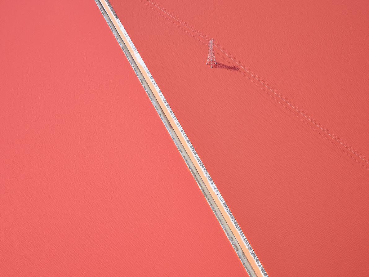 Stromtrasse über rosaroter Salzpfanne in Kalifornien
