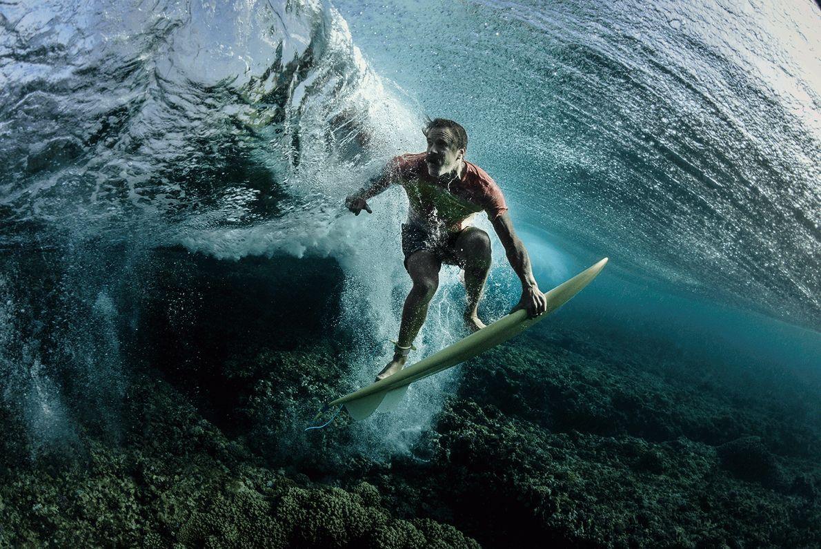 Ein Surfer auf seinem Board unter Wasser