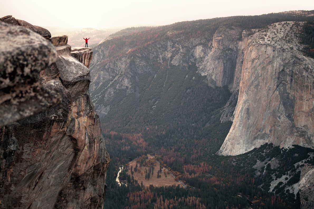 Ein Wanderer steht auf einem Klippenvorsprung im Yosemite Valley in Kalifornien, USA