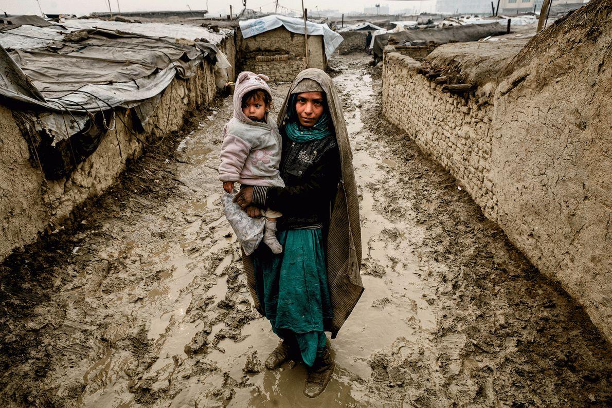 Eine innerhalb des Landes vertriebene, afghanische Frau mit ihrem Kind auf dem Arm