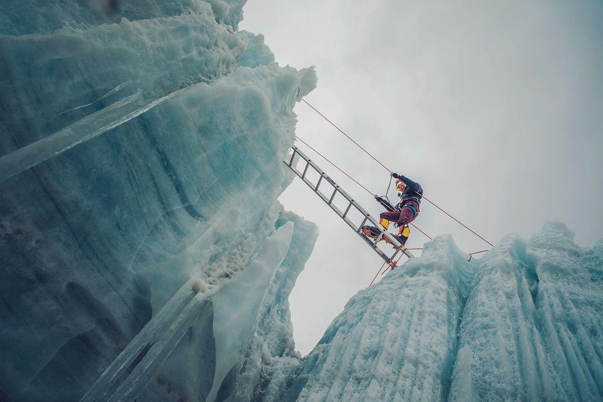 Eine Frau überquert eine Gletscherspalte im Himalaya