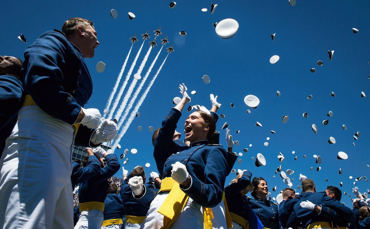 Kadetten der Air Force werfen auf ihrer Abschlussfeier ihre Mützen in die Luft