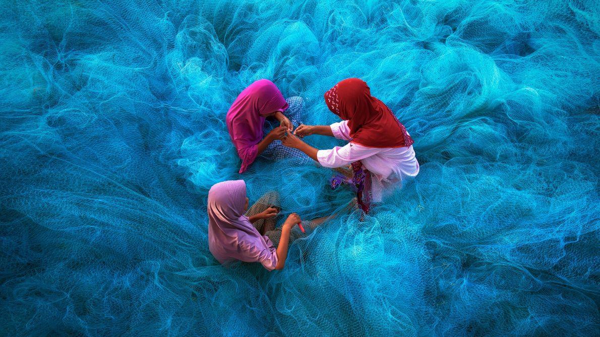In Nakhon Si Thammarat im Süden Thailands sitzt eine Familie in einem Haufen Fischernetze. Wenn man ...