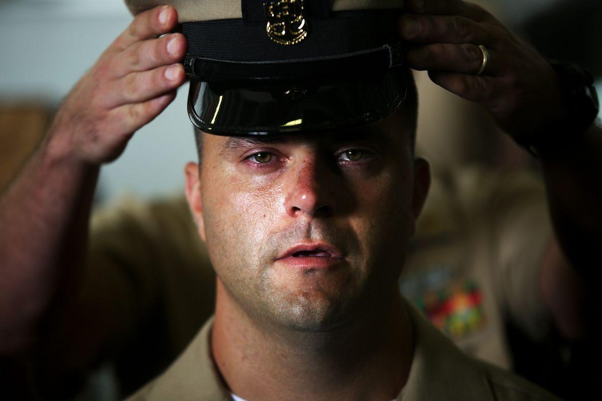 Mann bekommt Offizierskappe aufgesetzt