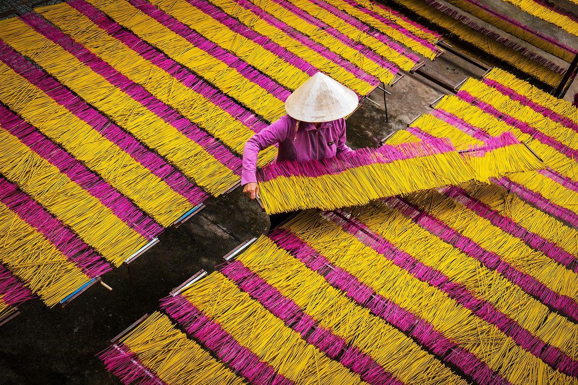 Eine Frau legt gelbe und rosafarbene Räucherstäbchen aus