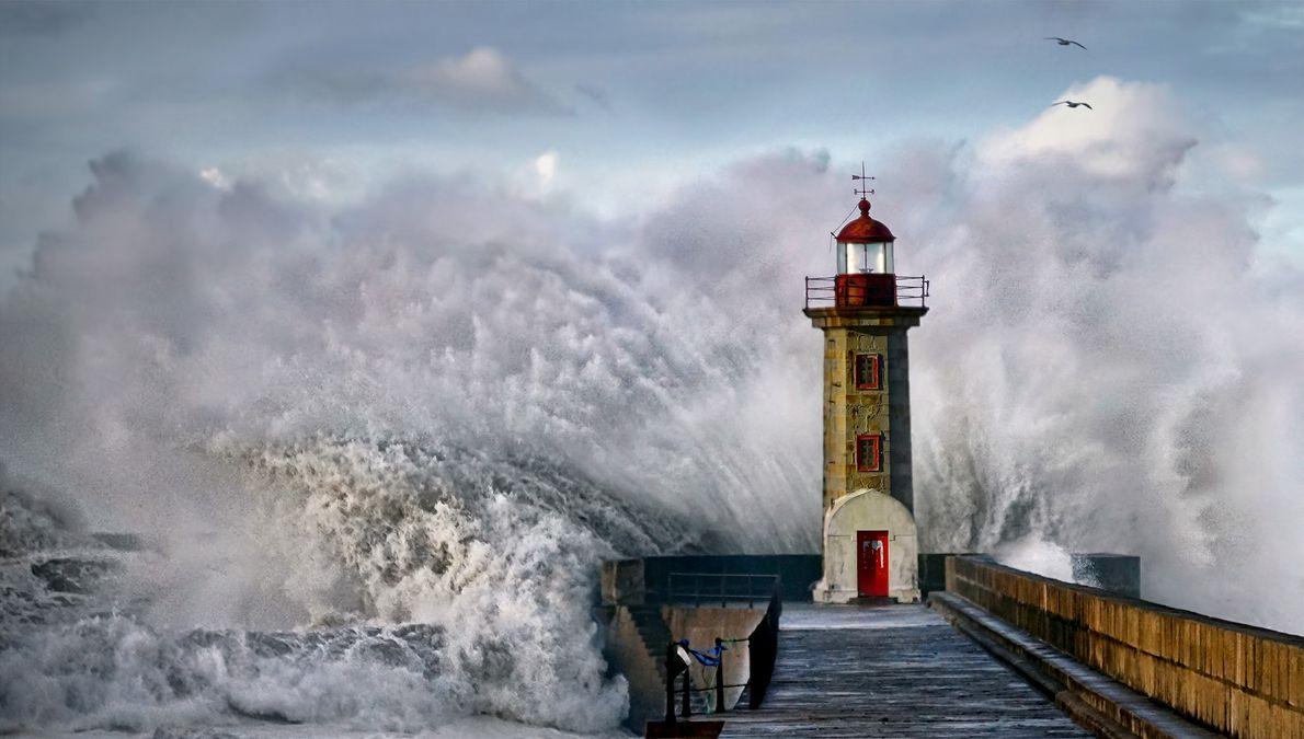 Eine Welle bricht sich an einem Leuchtturm in Portugal