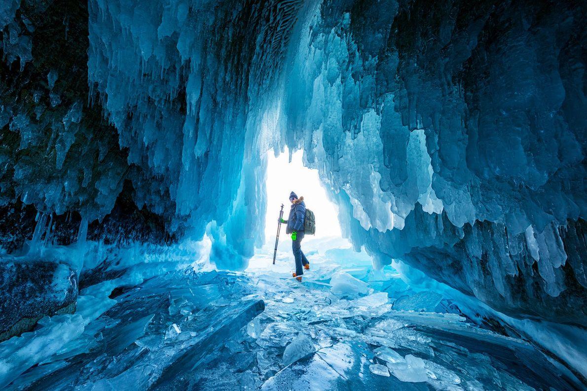 Ein Wanderer steht in einer Eishöhle