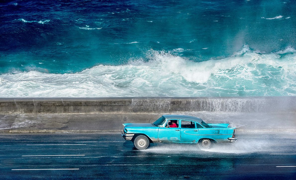 Ein blaues Auto fährt im kubanischen Havanna am Meer entlang