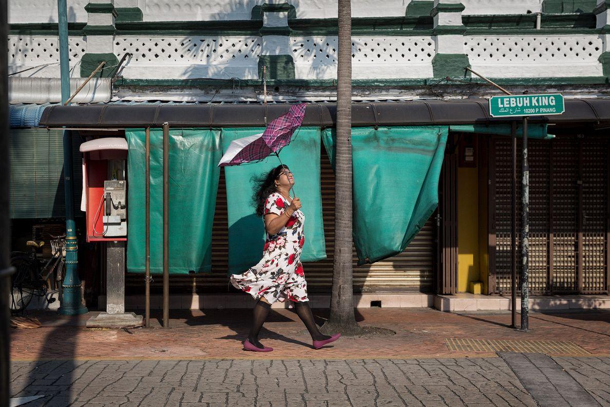 Eine Frau läuft mit einem defekten Regenschirm eine Straße entlang