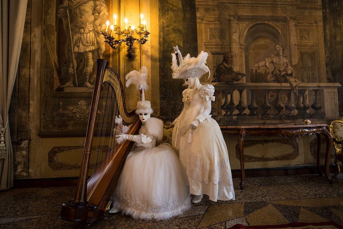 Zwei Menschen in traditionellen Karnevalskostümen und Masken posieren mit einer Harfe