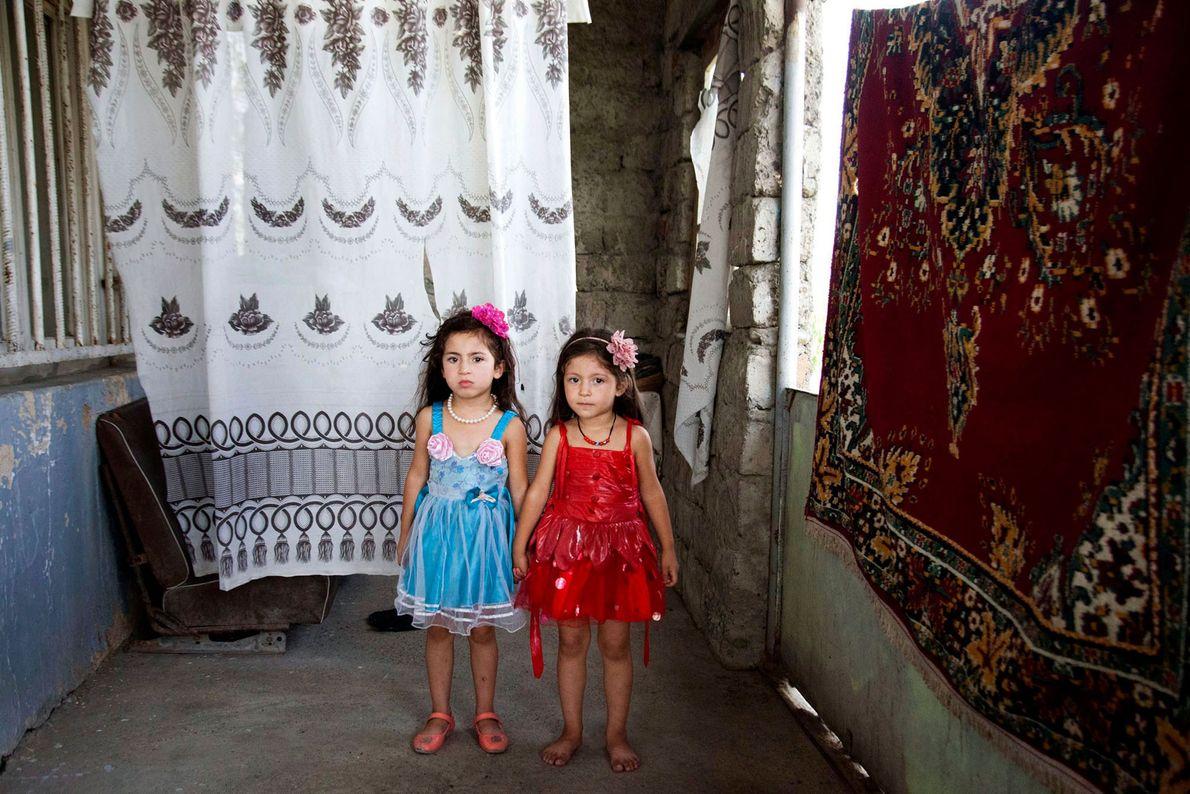 Foto von Zwillingen, die neben Wandteppichen stehen