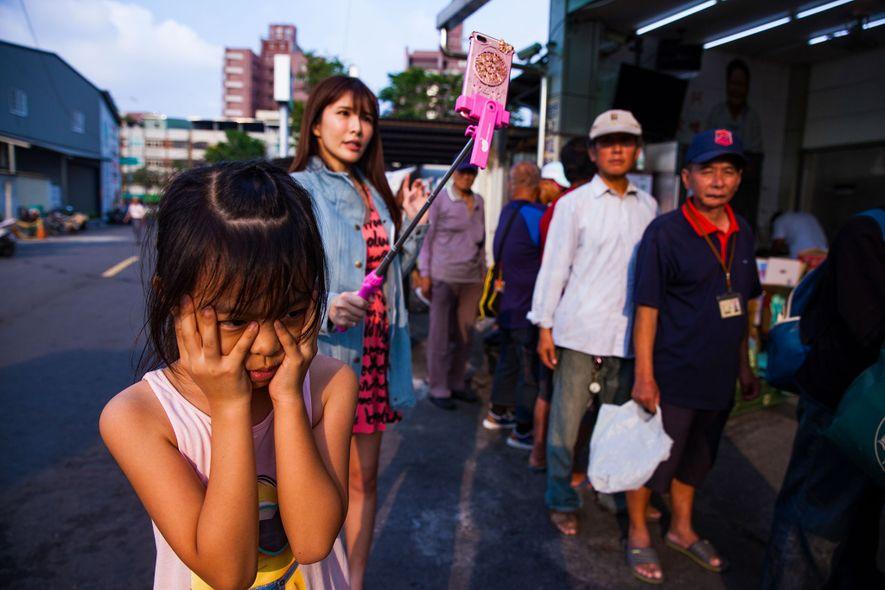 Mong Mong schaut weg, während ihre Mutter sich dabei filmt, wie sie zusammen mit einer lokalen ...
