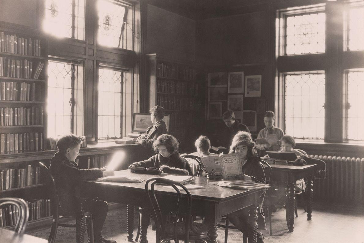 Schulkinder lesen und lernen in einer Bibliothek – eines von ihnen liest eine Ausgabe des National ...