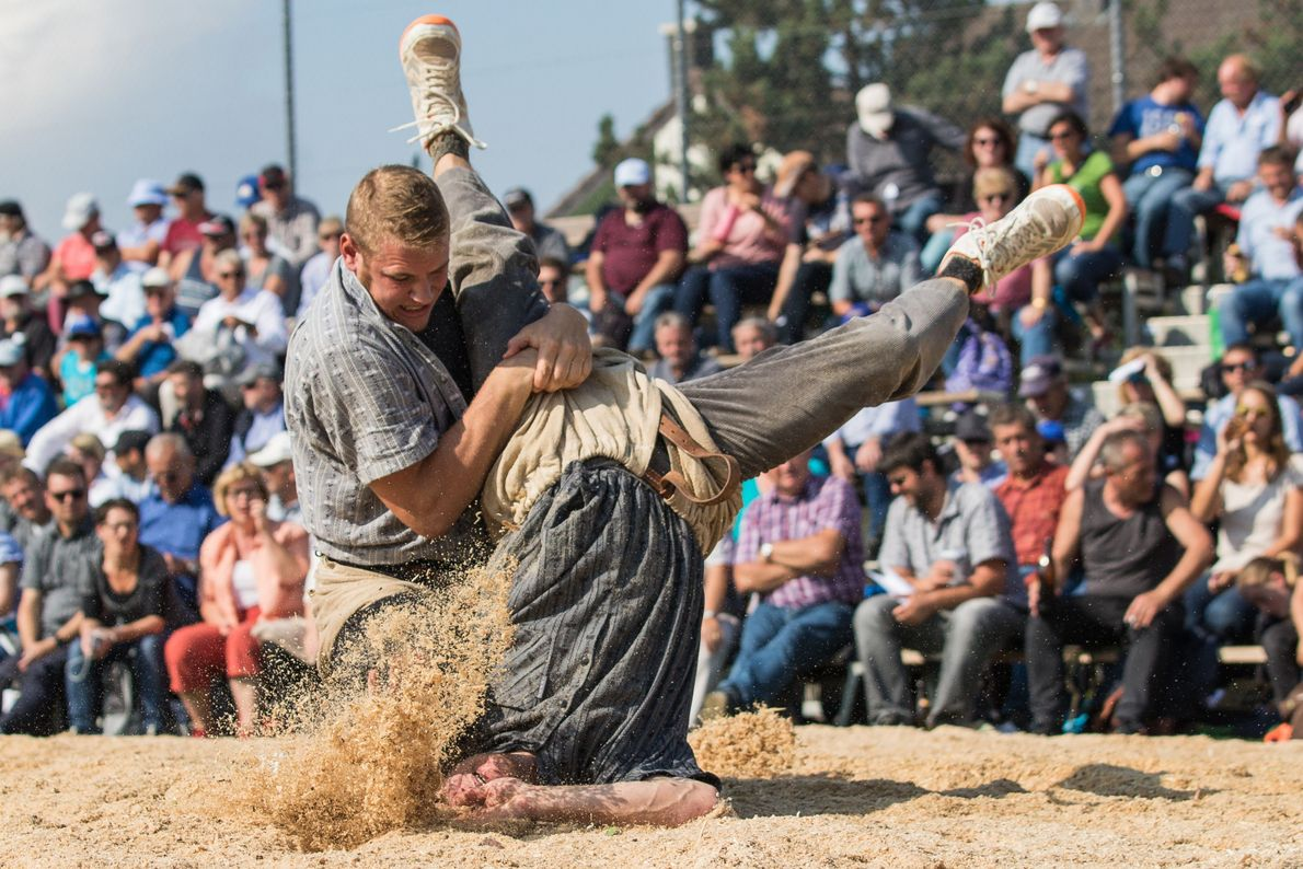 Two men engage in a bout of Schwingen, or Swiss wrestling. The traditional sport goes back ...